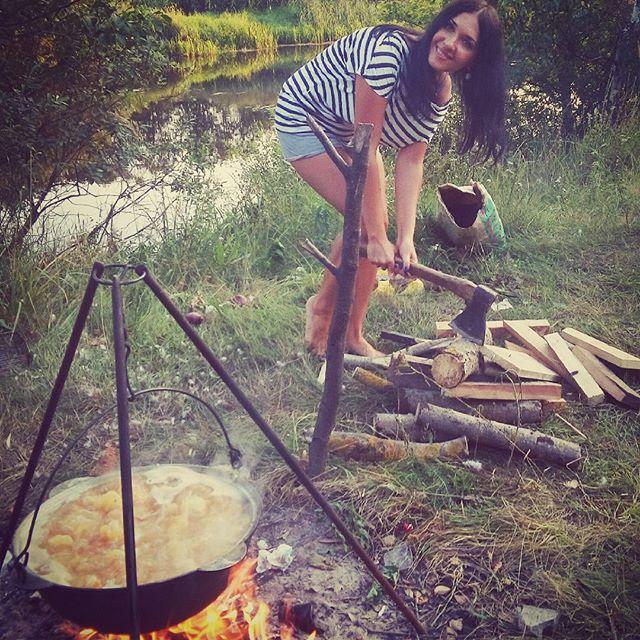 Девушка колит дрова топором